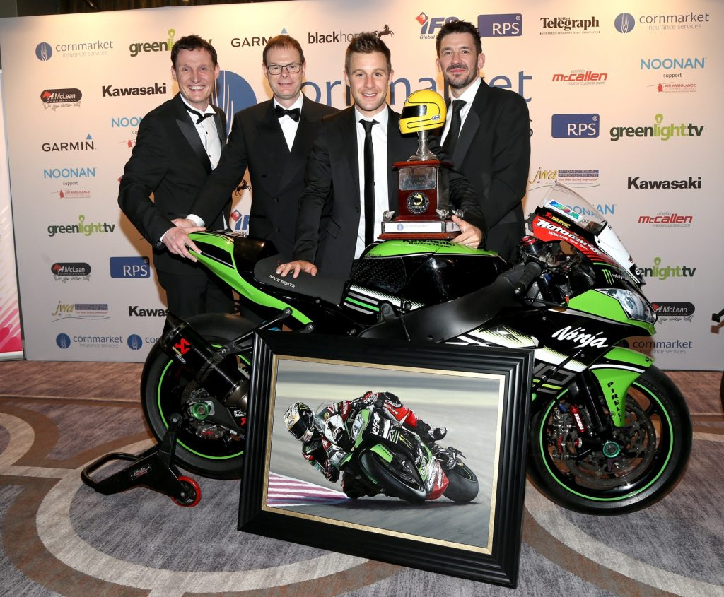 Billy with Howard Dale Kawasaki UK General Manager, Jonathan Rea and Craig Watson Kawasaki UK Sales Manager with Billy's oil painting in front of Jonathan's Factory Kawasaki ZX-10R Superbike. Jonathan has the Joey Dunlop Trophy which he won for the fourth time at the Cornmarket Bike Awards.